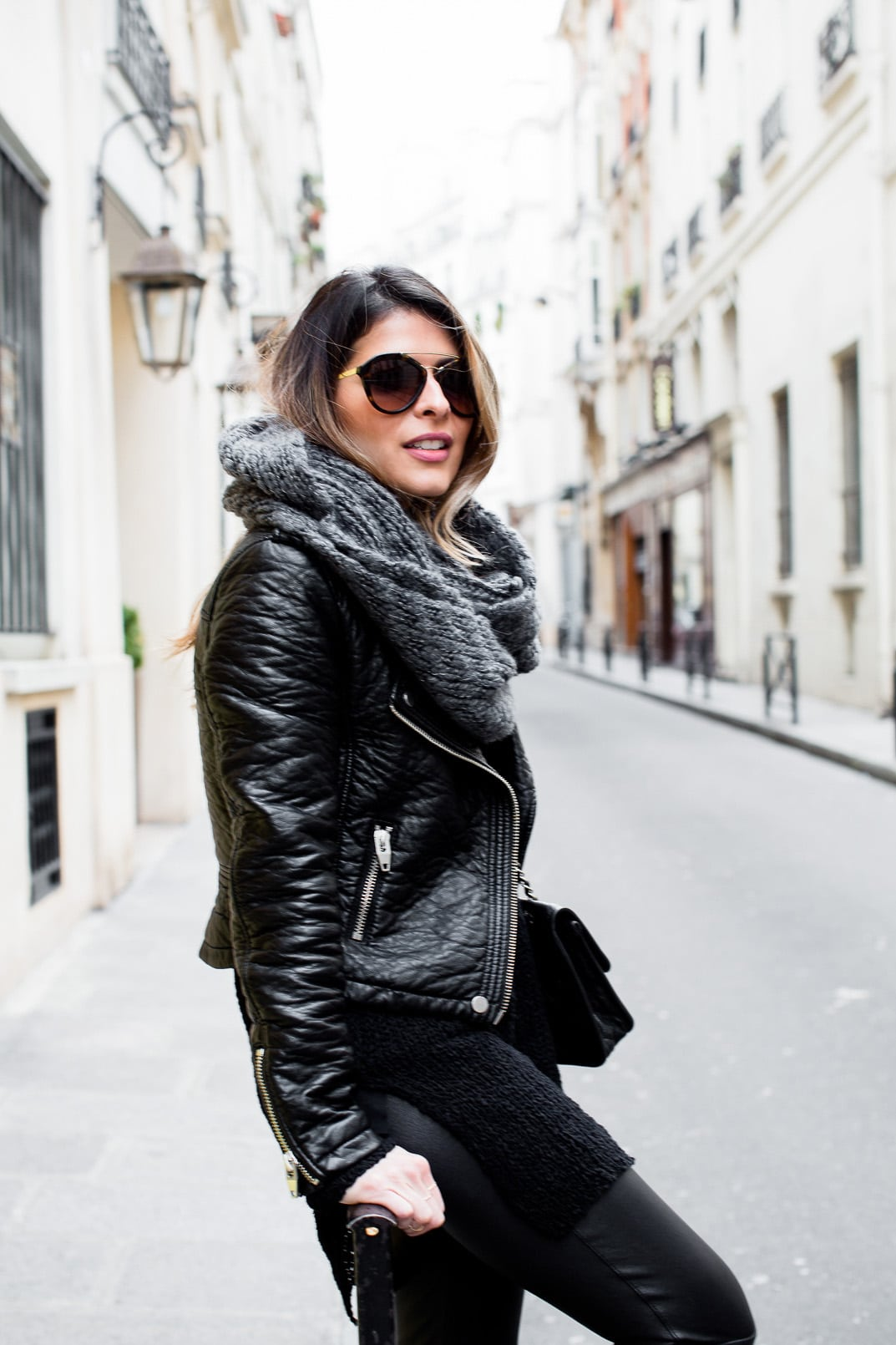 Pam Hetlinger wearing Leather Leggings, Faux-leather jacket, low-heeled booties, chunky scarf, and prada sunglasses. Paris. Travel Look.