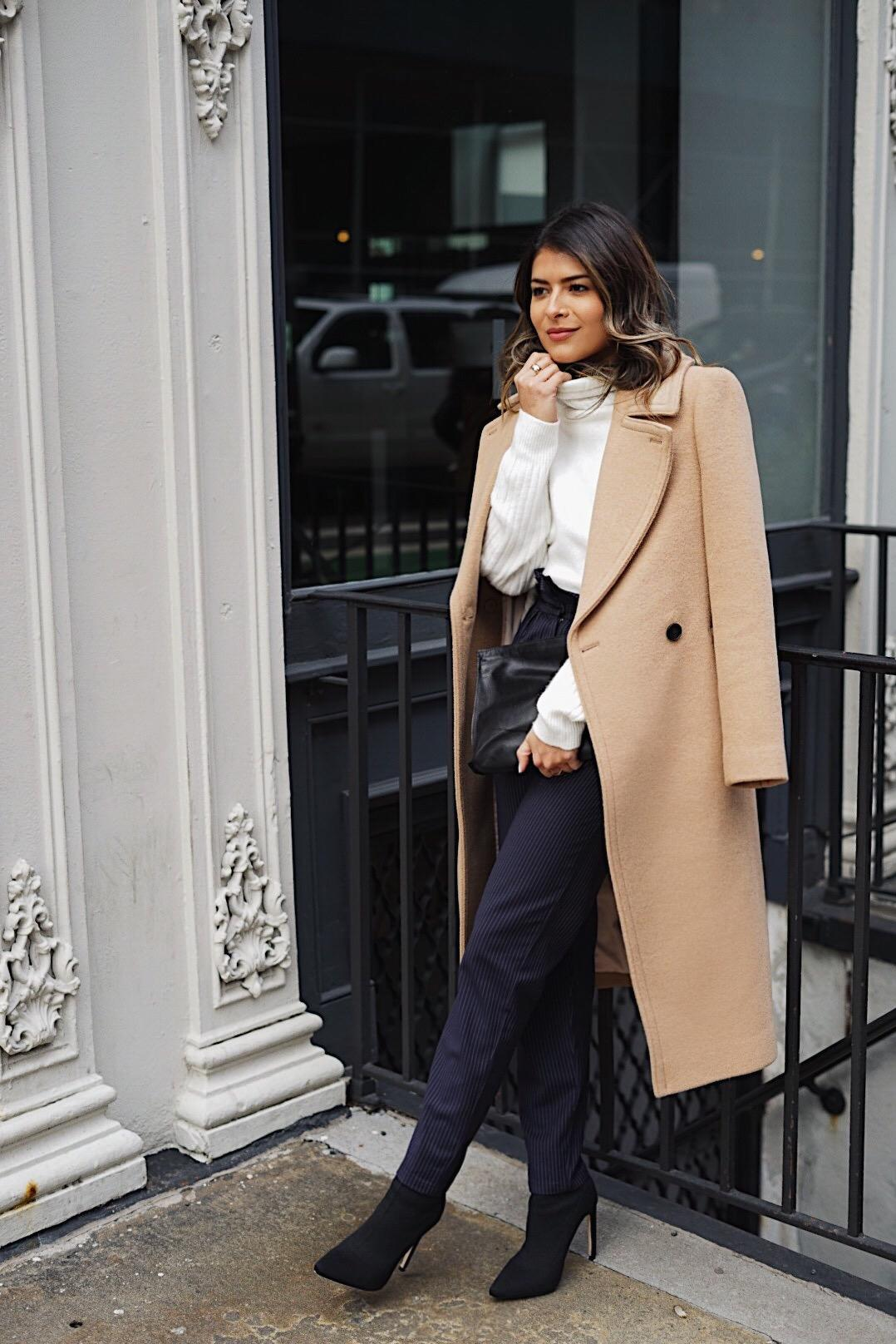 Pam Hetlinger styles high waisted navy and white striped trousers with a white turtleneck sweater and a camel suede coat.
